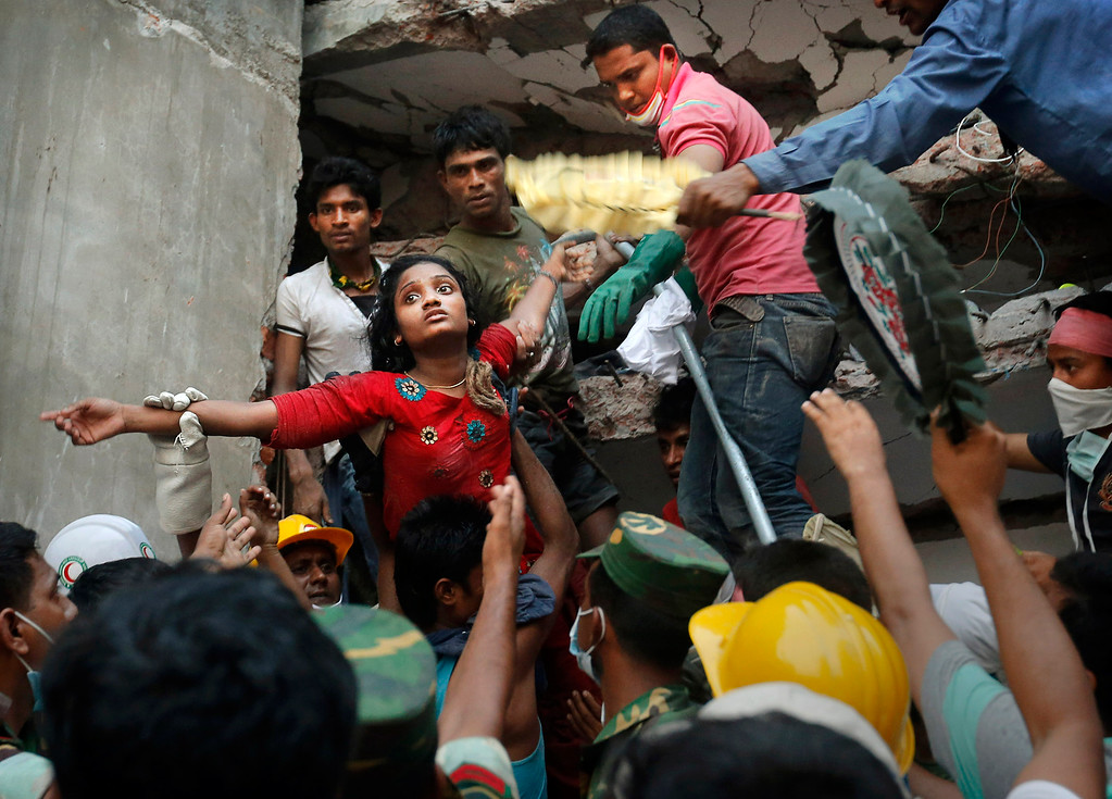 . A Bangladeshi woman survivor is lifted out of the rubble by rescuers at the site of a building that collapsed Wednesday in Savar, near Dhaka, Bangladesh, Thursday, April 25, 2013. The collapse of Rana Plaza in Dhaka that killed 1,129 people. (AP Photo/Kevin Frayer)
