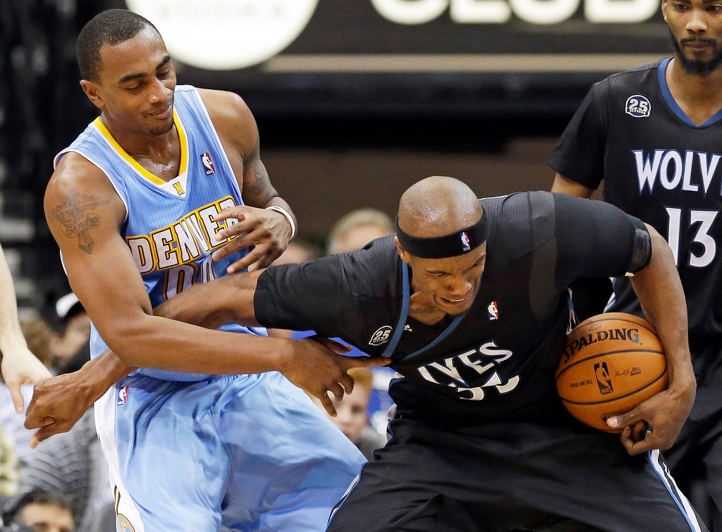 . Minnesota Timberwolves\' Dante Cunningham, right, tries to break away from Denver Nuggets\' Darrell Arthur in the second half of an NBA basketball game on Wednesday, Nov. 27, 2013, in Minneapolis. The Nuggets won 117-110. (AP Photo/Jim Mone)