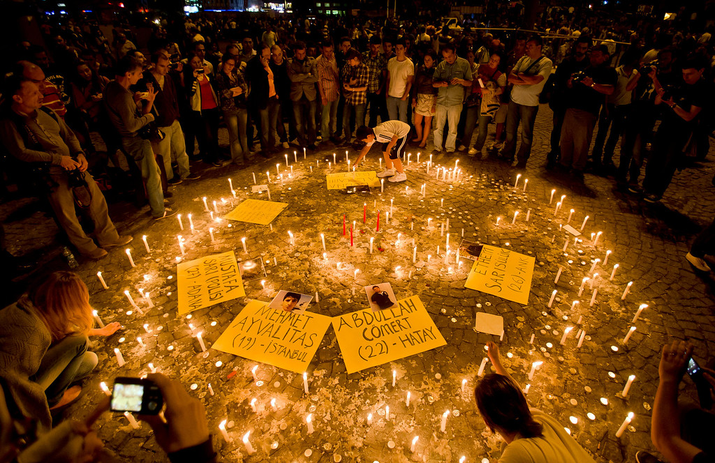 . People light candles for the victims of the protests at Taksim square, in Istanbul, early Saturday, June 15, 2013. Protesters were holding debates in several locations in Gezi Park to discuss the results of a meeting with the prime minister and whether his proposal was enough for them to end their occupation of the park. (AP Photo/Vadim Ghirda)
