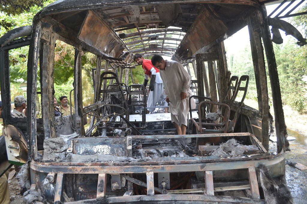 . Pakistani security personnel inspect a burnt university bus after a bomb blast in Quetta, the capital of Baluchistan province, on June 15, 2013.   AFP PHOTO/ Banaras KHAN/AFP/Getty Images