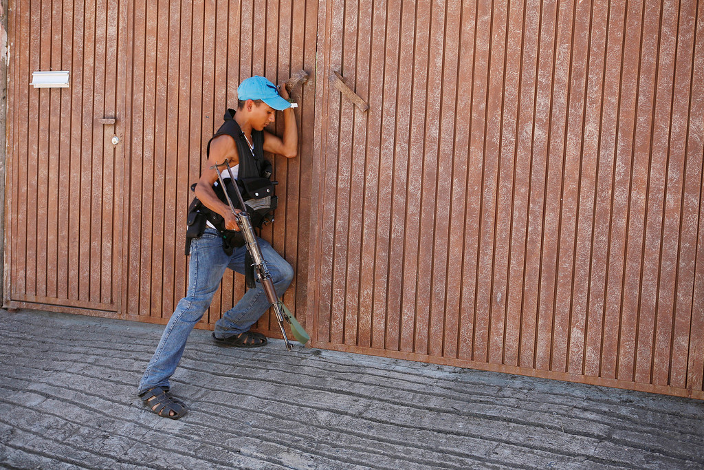 . A young man, who identifies himself as M3, tries to enter the home of an alleged member of the Templar Knights cartel in the town of Aguililla, Mexico, Thursday, July 25, 2013. The 18-year-old, who claims on a video posted on a national newspaper website, that he is a former Templar Knights gunman who deserted the cartel and joined the ranks of the Aguililla self-defense group because he was disgusted with the way the Templar Knights treat the community. (AP Photo/Gustavo Aguado)