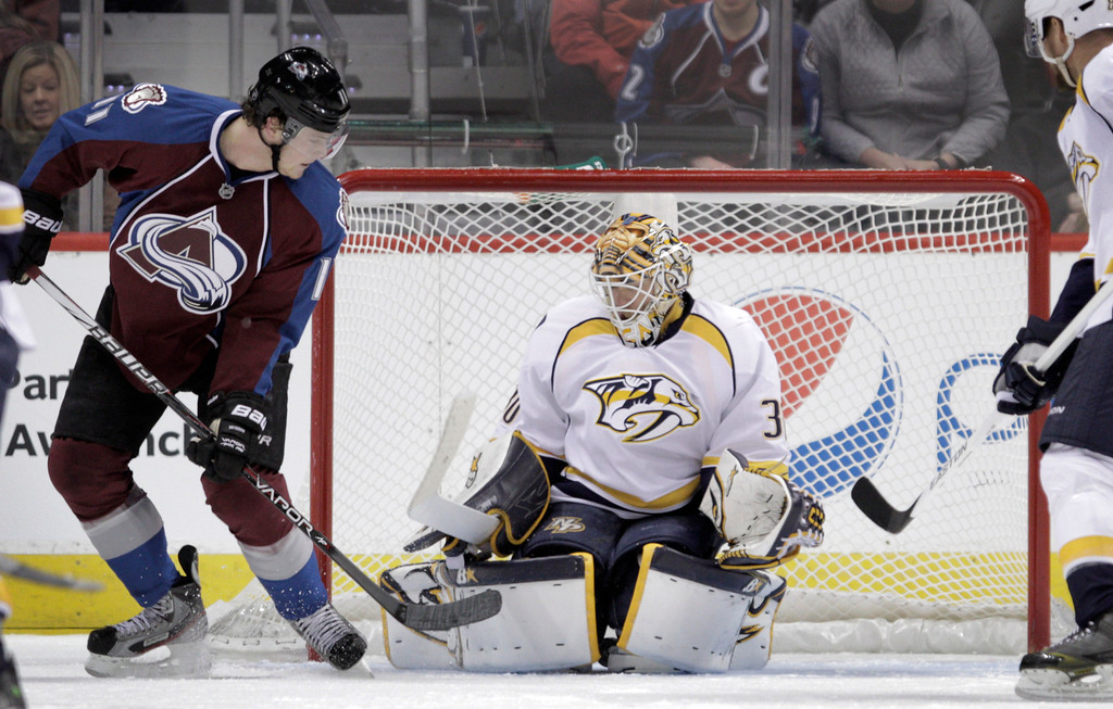 . The puck gets past Nashville Predators goalie Chris Mason (30) for a goal by Colorado Avalanche defenseman Tyson Barrie (41), not shown, as Colorado Avalanche left wing Jamie McGinn (11) watches during the first period of an NHL hockey game, Monday, Feb. 18, 2013, in Denver.(AP Photo/Joe Mahoney)