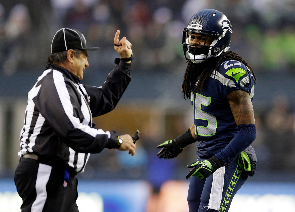 . Seattle Seahawks cornerback Richard Sherman, right, protests a play to an official in the second half of an NFL football game against the Arizona Cardinals, Sunday, Dec. 22, 2013, in Seattle. The Cardinalswon 17-10. (AP Photo/Elaine Thompson)