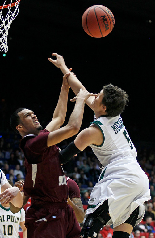 . Texas Southern forward Jose Rodriguez, left, and Cal Poly guard Reese Morgan (5) rebound in the first half of a first-round game of the NCAA college basketball tournament on Wednesday, March 19, 2014, in Dayton, Ohio. (AP Photo/Skip Peterson)