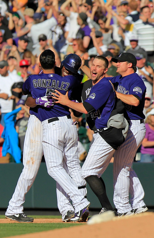 . Colorado Rockies\' Dexter Fowler, second from left, celebrates his game-winning RBI-single during the bottom of the 10th inning of a baseball game against the Los Angeles Dodgers, Saturday June 1, 2013 in Denver. The Rockies won 7-6. (AP Photo/Barry Gutierrez)