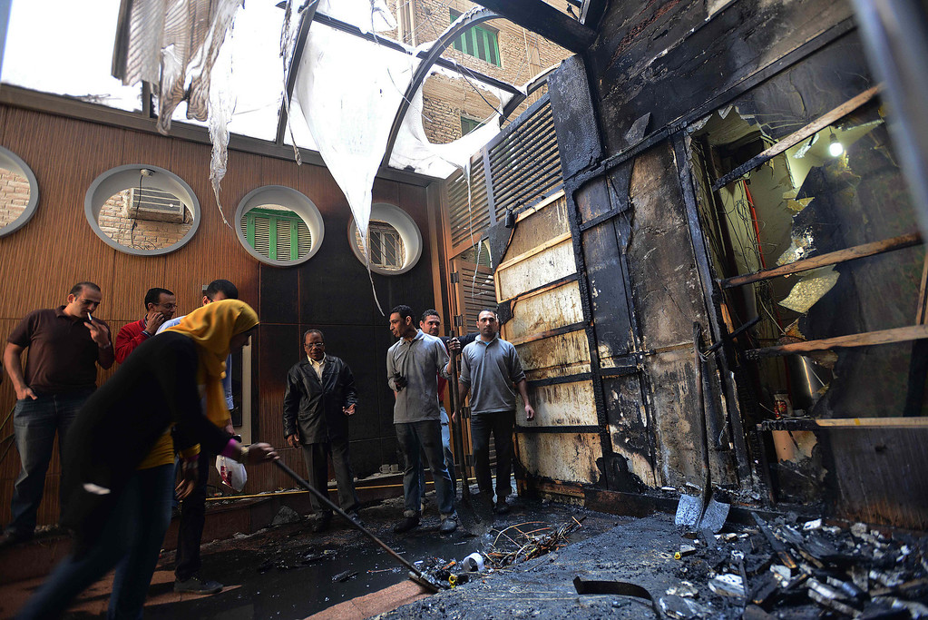 . Egyptian employees clear remains after a fire, set by an angry group, damaged the offices of local newspaper al-Watan on March 9, 2013 in the Egyptian capital Cairo.  AFP PHOTO /  AL-WATAN NEWSPAPER  /STR-/AFP/Getty Images