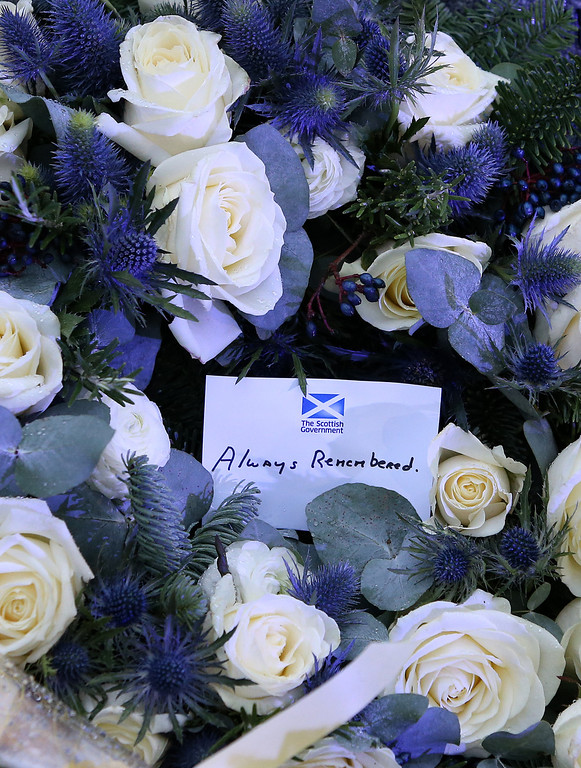 . A handwritten card is seen on a wreath laid by the main memorial stone in memory of the victims of the Pan Am flight 103 bombing in the garden of remembrance at Dryfesdale Cemetery, near Lockerbie, Scotland, Saturday, Dec. 21, 2013. (AP Photo/Scott Heppell).