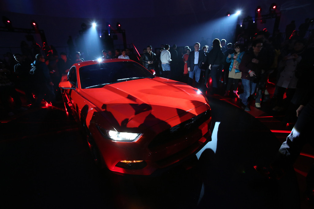. Guests look at the latest Mustang of the Ford Motor Company which is being unveiled at the All-New Ford Mustang Global Reveal event in Shanghai, China, Thursday, Dec. 5, 2013. (AP Photo/Eugene Hoshiko)