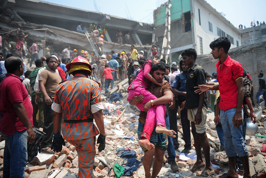 . A Bangladeshi volunteer carries an injured garment worker after an eight-story building collapsed in Savar, on the outskirts of Dhaka, on April 24, 2013. AFP PHOTO/Munir UZ ZAMAN/AFP/Getty Images