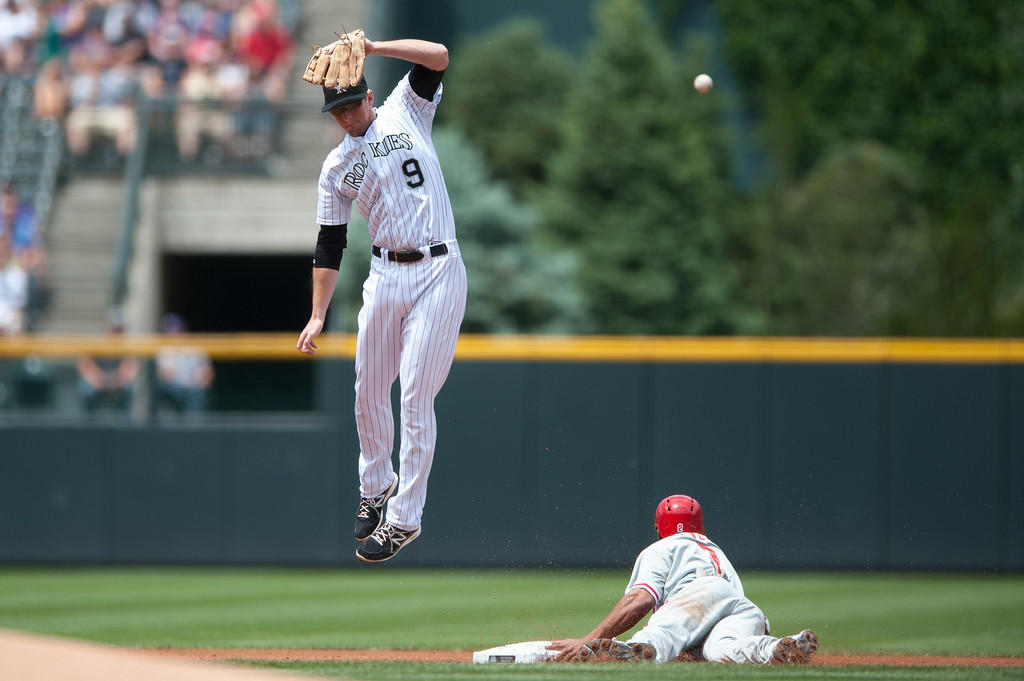 . DENVER, CO - JUNE 15:  Ben Revere #2 of the Philadelphia Phillies slides and steals second base as DJ LeMahieu #9 of the Colorado Rockies leaps for an overthrown ball in the first inning of a game at Coors Field on June 15, 2013 in Denver, Colorado.  (Photo by Dustin Bradford/Getty Images)