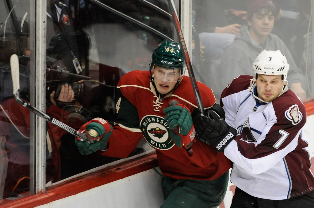 . ST PAUL, MN - JANUARY 19:  John Mitchell #7 of the Colorado Avalanche checks Justin Falk #44 of the Minnesota Wild into the boards during the first period of their home opener on January 19, 2013 at Xcel Energy Center in St Paul, Minnesota. (Photo by Hannah Foslien/Getty Images)