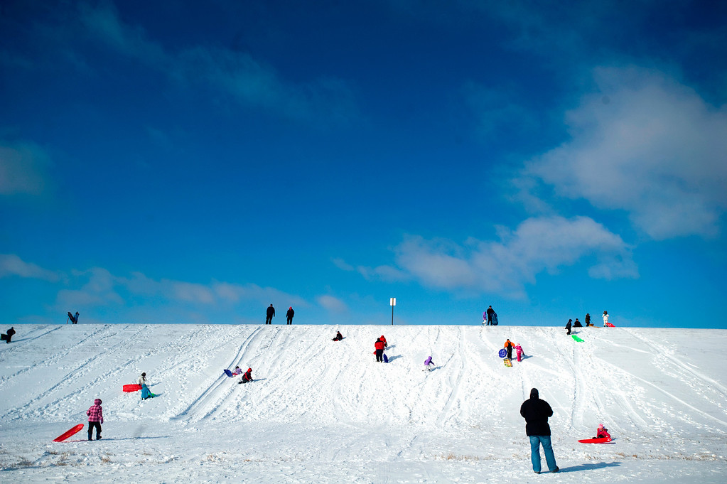 . Sledders enjoy the snow on Thursday, Dec. 20, 2012 at Holmes Lake in Lincoln, Neb. (AP Photo/The Journal-Star, Adam Wolffbrandt) LOCAL TV OUT; KOLN-TV OUT; KGIN-TV OUT; KLKN-TV OUT