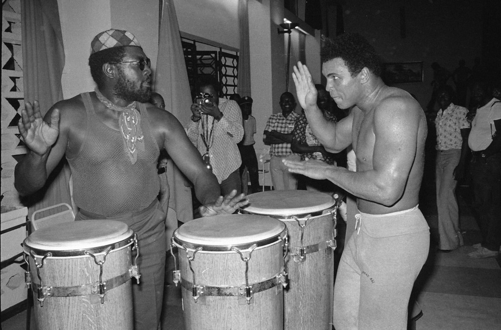 """. Heavyweight contender Muhammad Ali plays the bongos with \""""Big Black\"""" at a gym in the N\'Sele training center in Zaire, Oct. 5, 1974.  Ali is training for a bout with George Foreman.  (AP Photo/Horst Faas)"""