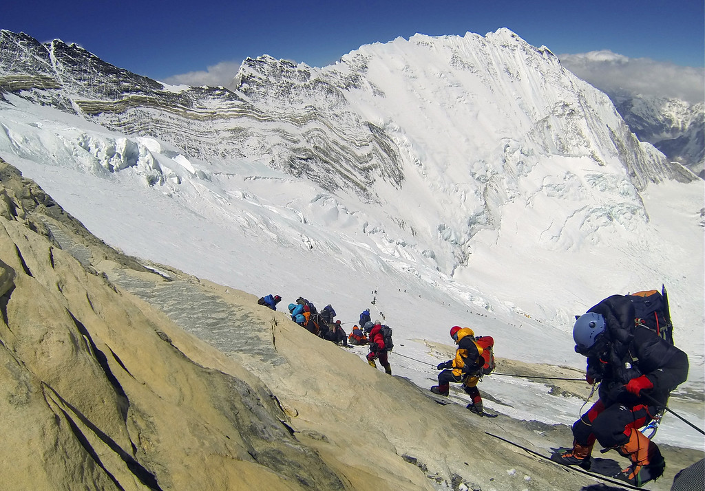 . In this Saturday, May 18, 2013 photo, climbers from various countries make their way down towards Camp 4 on their way to summit the 8,850-meter (29,035-foot) Mount Everest. May is the most popular month for Everest climbs because of more favorable weather. Earlier this month, an 80-year-old Japanese man Yuichiro Miura became the oldest conqueror of Mount Everest and Raha Moharrak became the first woman from Saudi Arabia to scale the peak. (AP Photo/ Pasang Geljen Sherpa)