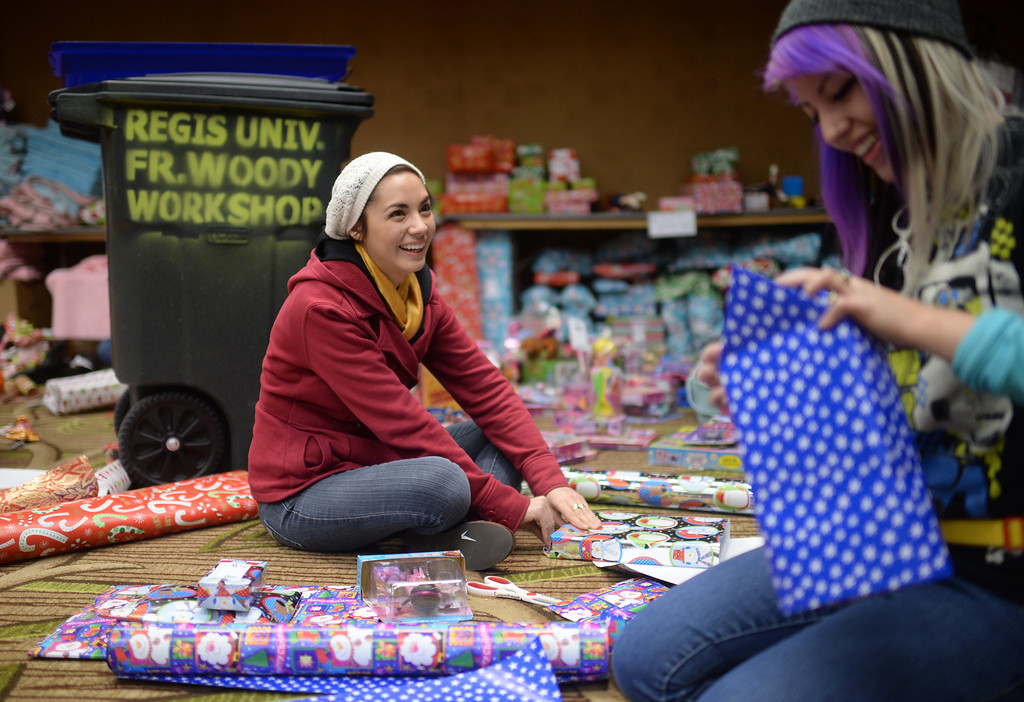 """. DENVER, CO. DECEMBER 21: Andreina Lujan, 19, of Denver, left, and her sister Alejandra, 21, are  wrapping Christmas gift during the annual Father Woody Christmas Party in Denver, Colorado December 21, 2013. In advance of handing out 5,000 gifts, volunteers are doing a \""""wrapping party\"""" at the Sheraton Denver Downtown Hotel. (Photo by Hyoung Chang/The Denver Post)"""