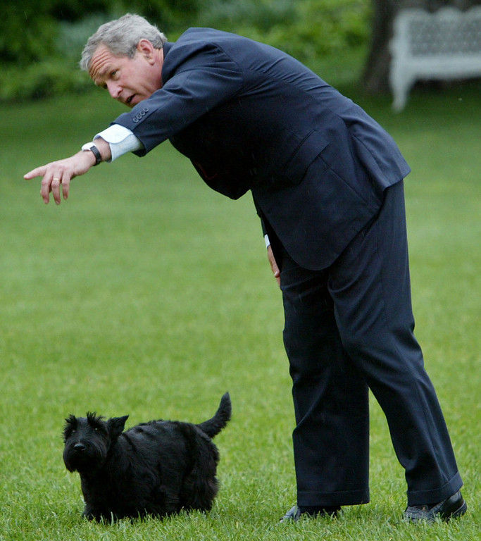 . President Bush points in the direction his dog, Barney, should go following his arrival on Marine One helicopter on the South Lawn of the White House Monday, May 5, 2003 in Washington. The president earlier visited Arkansas on his way back to Washington following a weekend at his Texas ranch. (AP Photo/Pablo Martinez Monsivais)