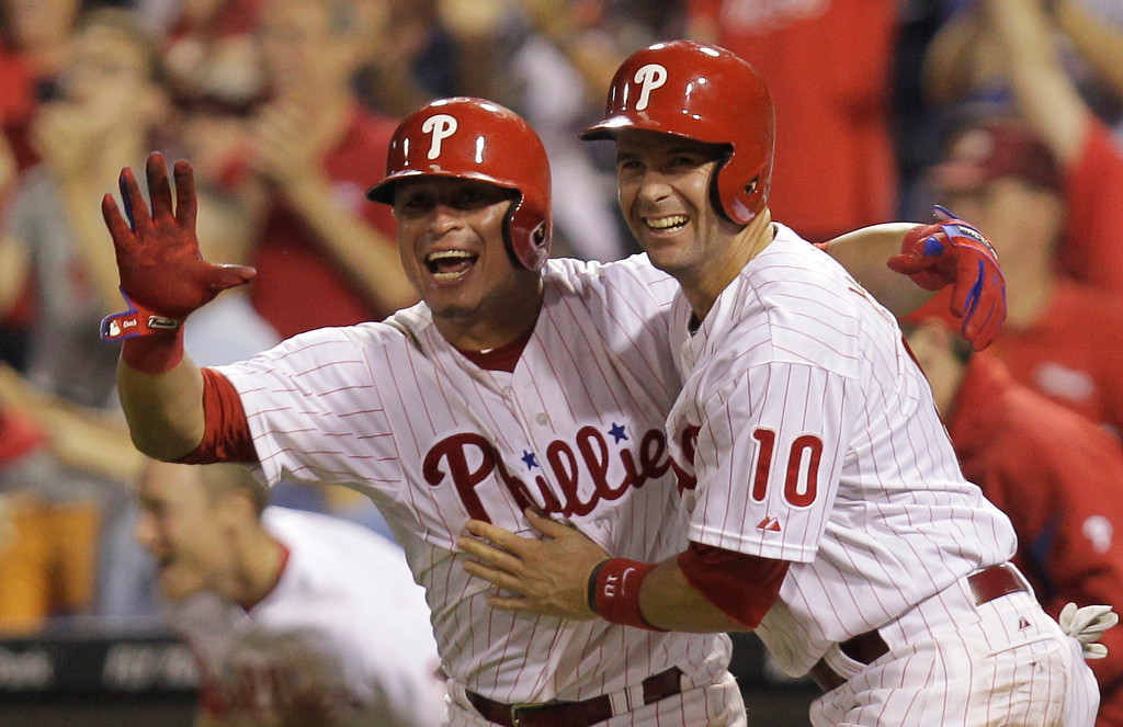 . Philadelphia Phillies\' Michael Young, right, is cheered by teammate Carlos Ruiz after making the game-winning run on a hit by Domonic Brown in the ninth inning of a baseball game to defeat the Colorado Rockies 5-4, Thursday, Aug. 22, 2013, in Philadelphia. (AP Photo/Laurence Kesterson)