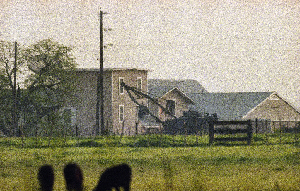 . A battering ram attached to an armored vehicle moves in front of the Branch Davidian compound near Waco, Texas on Monday, April 19, 1993. The armored vehicle ripped into the compound, tearing down and punching large holes on the 51st day of a standoff. (AP Photo/Ron Heflin)