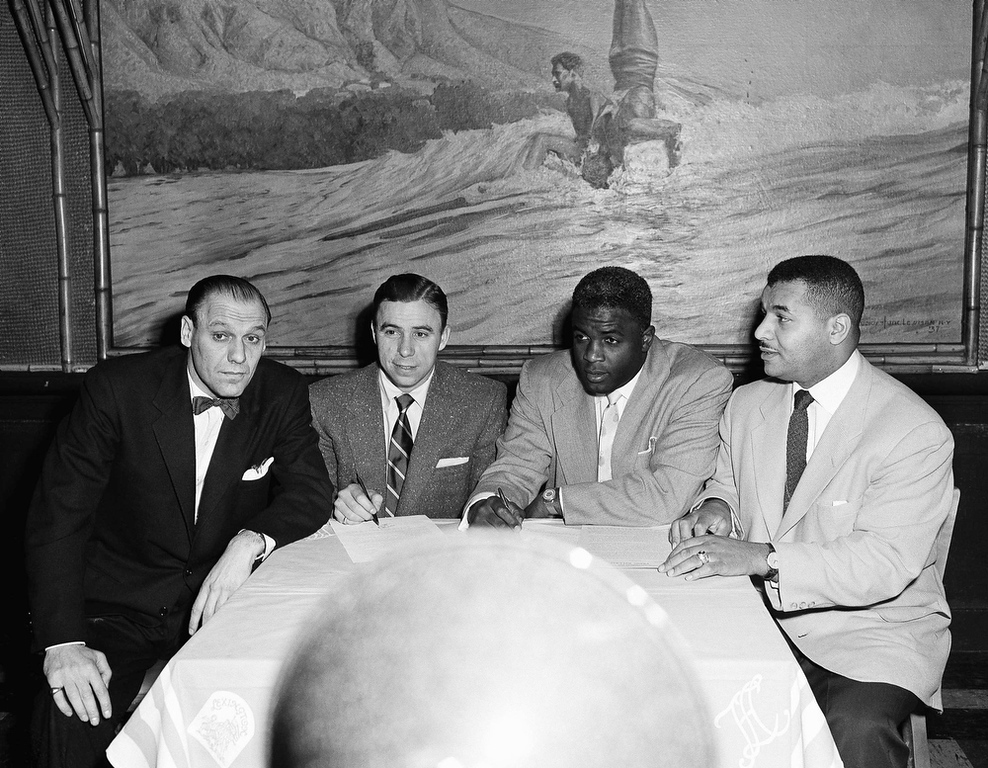 ". In this Jan. 11,1953 photo, Brooklyn Dodgers vice president E.J. ""Buzzie\"" Bavasi, left, sits with players Harold \""Pee Wee\"" Reese, second from left, Jackie Robinson, second from right, and Roy Campanella at the Hotel Lexington in New York.  Bavasi, who built Dodgers teams that won the World Series in Brooklyn and Los Angeles. (AP Photo)"