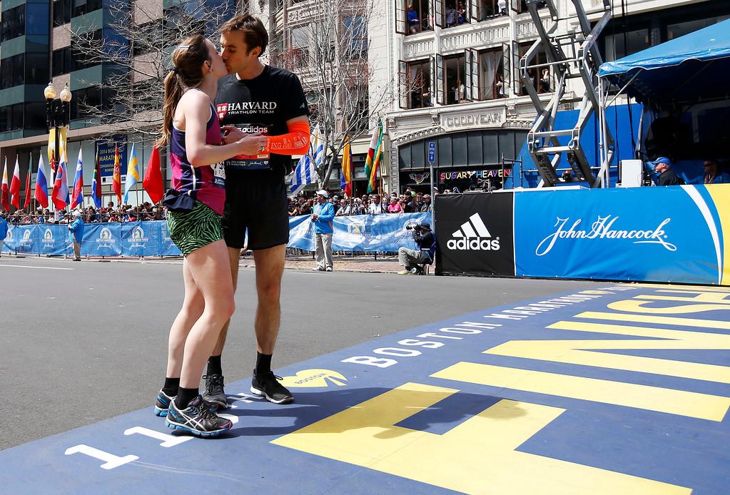 . Devin Parker, of Hanover, N.H., kisses John T. Heineman, of Iowa City, Iowa, as they cross the finish line of the 118th Boston Marathon, Monday, April 21, 2014, in Boston. (AP Photo/Elise Amendola)
