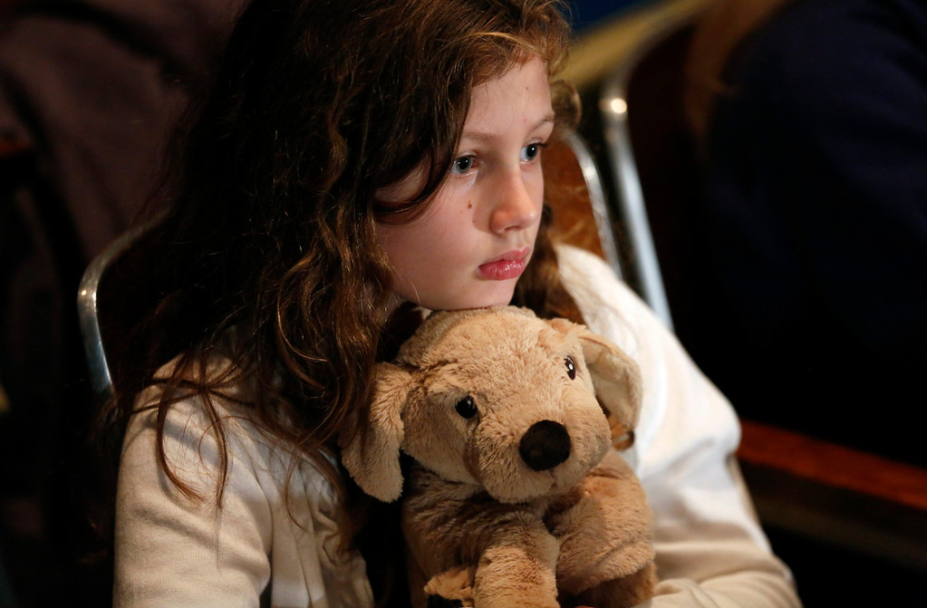 . A girl holds a stuffed animal given to her by the Red Cross during a vigil held at Newtown High School for families of victims of the Sandy Hook Elementary School shooting in Newtown, Connecticut December 16, 2012. U.S. President Barack Obama is visiting Newtown High School to meet with the families of the victims and to thank first responders to the school shooting here that was one of the deadliest such incidents in the nation\'s history. REUTERS/Kevin Lamarque