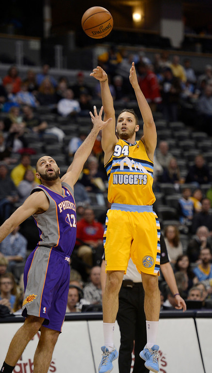 . Evan Fournier (94) of the Denver Nuggets takes a shot over Kendall Marshall (12) of the Phoenix Suns during the first quarter April 17,  2013 at Pepsi Center. (Photo By John Leyba/The Denver Post)