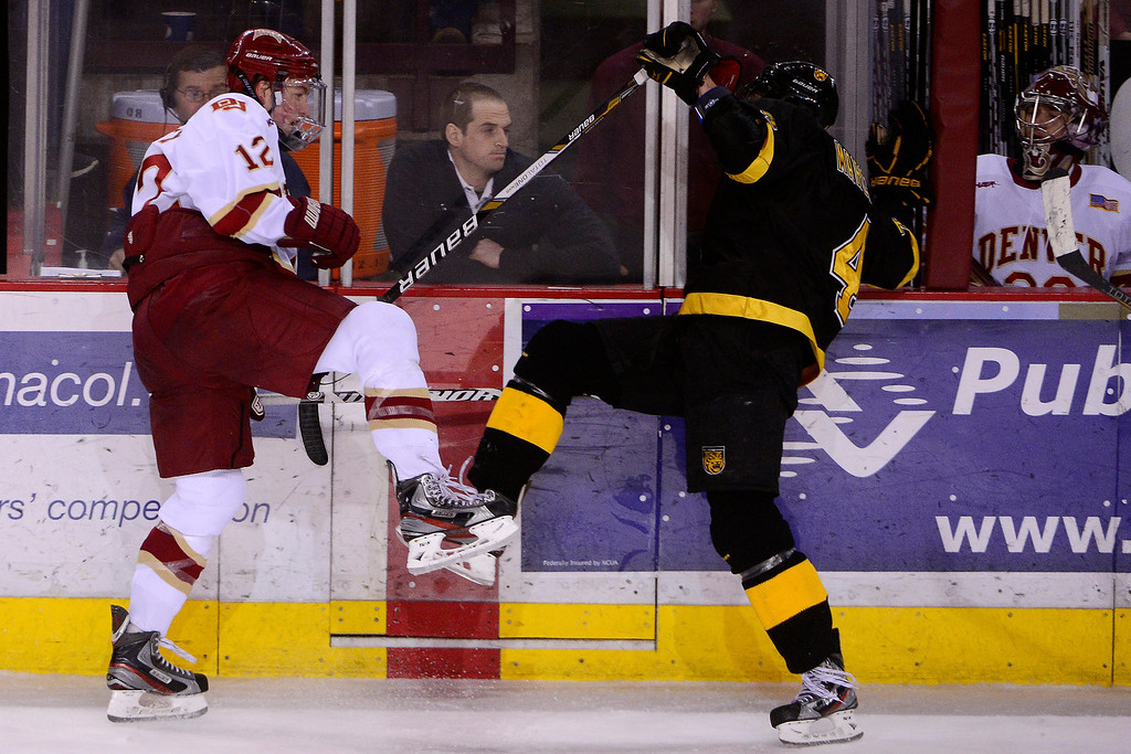 . DENVER, CO - MARCH 17: Ty Loney (12) of the University of Denver Pioneers and Joe Marciano (4) of the Colorado College Tigers tangle during the second period of action. The University of Denver and Colorado College face off in the WCHA playoffs at Magness Arena. (Photo by AAron Ontiveroz/The Denver Post)