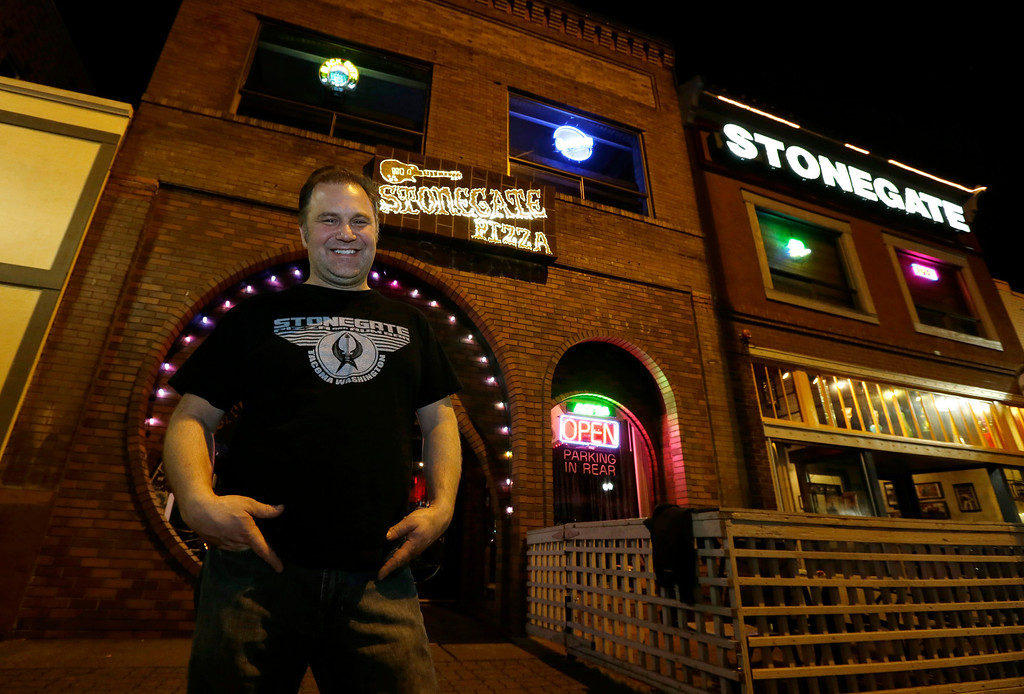 """. Jeff Call, owner of the Stonegate pizza-and-rum bar, poses for a photo in front of his business, Saturday, March 2, 2013, in Tacoma, Wash. Call charges patrons a small fee to become a member of the private second-floor club in the lounge area upstairs, which allows \""""vaporizing,\"""" marijuana, a method that involves heating the marijuana without burning it. Last fall, Washington and Colorado became the first states to legalize marijuana use for adults over 21. (AP Photo/Ted S. Warren)"""