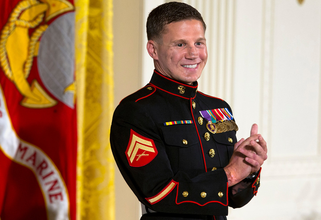 """. Retired Marine Cpl. William \""""Kyle\"""" Carpenter applauds his medical team as they stand to be acknowledged by President Barack Obama during a ceremony presenting Carpenter with the Medal of Honor for conspicuous gallantry, Thursday, June 19, 2014, in the East Room of the White House in Washington. Carpenter received the Medal of Honor for his courageous actions while serving as an Automatic Rifleman in Helmand Province, Afghanistan. (AP Photo/Jacquelyn Martin)"""