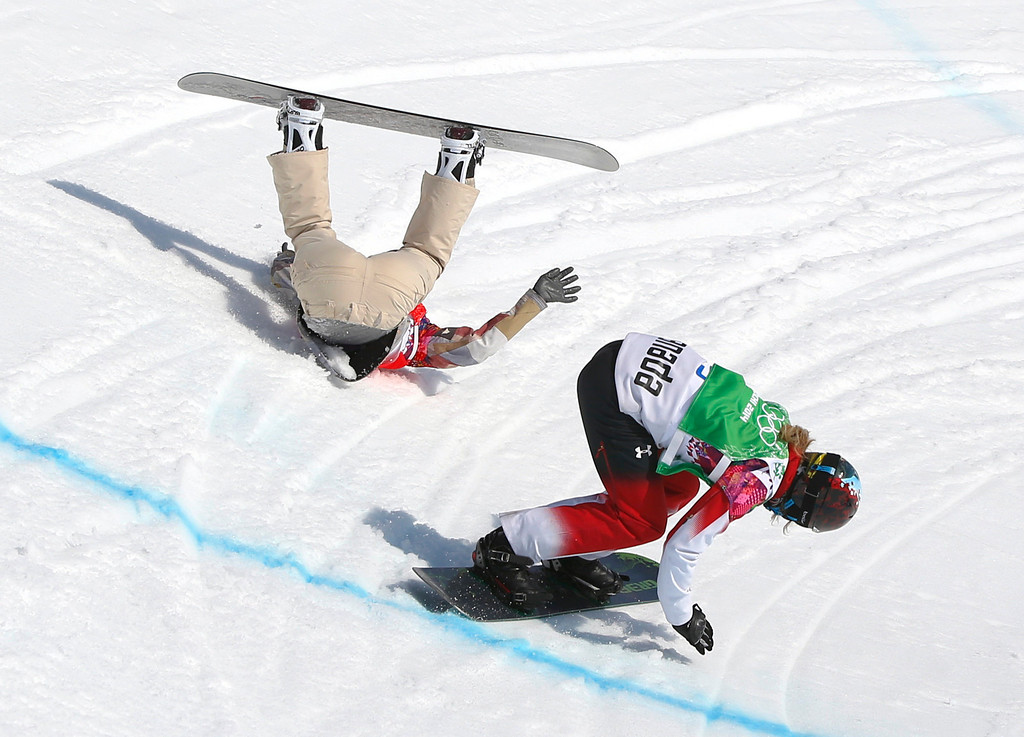 . Lindsey Jacobellis of the United States crashes in the women\'s snowboard cross semifinal as Canada\'s Dominique Maltais. tries to avoid her at the Rosa Khutor Extreme Park, at the 2014 Winter Olympics, Sunday, Feb. 16, 2014, in Krasnaya Polyana, Russia.   (AP Photo/Sergei Grits)