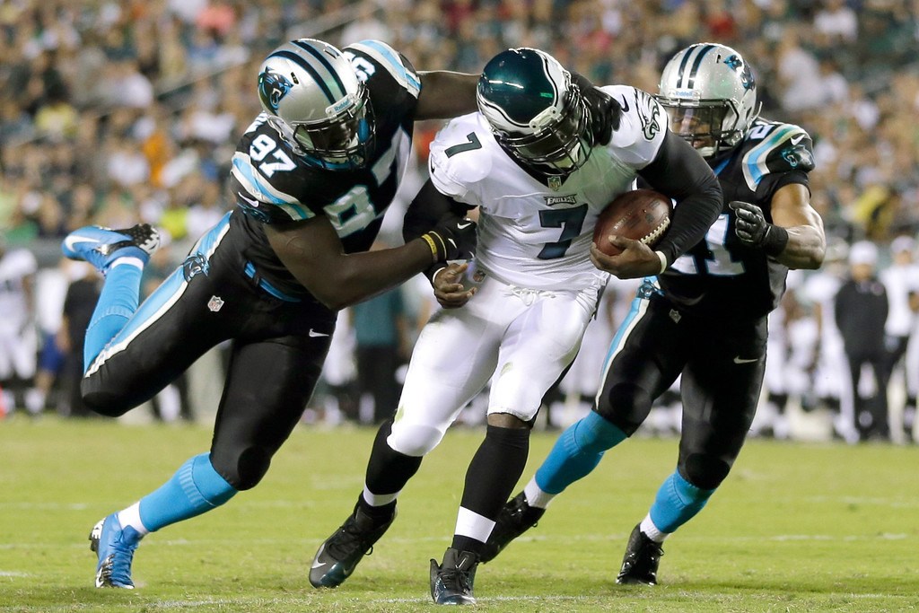 . Philadelphia Eagles quarterback Michael Vick, center, is tackled by Carolina Panthers defensive end Mario Addison, left, and safety Mike Mitchell during the first half of a preseason NFL football game, Thursday, Aug. 15, 2013, in Philadelphia. (AP Photo/Matt Rourke)