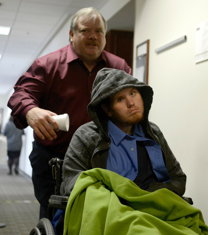 . Aurora theater shooting victim Caleb Medley and his father Otis Medley leave the second floor of the Arapahoe County Courthouse, Tuesday March 12, 2013 after the proceedings. District Court Judge William Sylvester entered a Not Guilty plea on behalf of Holmes.(Photo By Joe Amon/The Denver Post)