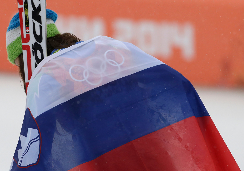 . Women\'s giant slalom gold medal winner Tina Maze of Slovenia leaves the podium draped in her national flag after a flower ceremony at the Sochi 2014 Winter Olympics, Tuesday, Feb. 18, 2014, in Krasnaya Polyana, Russia.  (AP Photo/Gero Breloer)