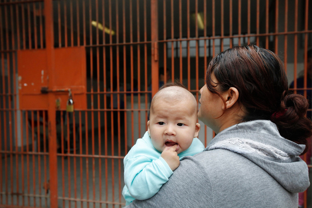 . An inmate carries her baby next to a cell during celebrations for Mother\'s Day at the Santa Monica female prison in Lima, May 10, 2013. New nursery facilities for the inmates\' babies were inaugurated by Peru\'s prison authorities to improve the care and education of 40 children that are permitted to stay with their mothers in the prison till they are three-years-old. REUTERS/Enrique Castro-Mendivil