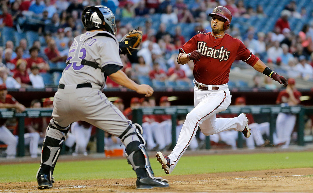 . Arizona Diamondbacks\' Martin Prado, right, tries to score on a base hit by teammate Paul Goldschmidt as Colorado Rockies catcher Jordan Pacheco waits for the throw during the first inning of a baseball game on Wednesday, April 30, 2014, in Phoenix. Prado was out on the play. (AP Photo/Matt York)
