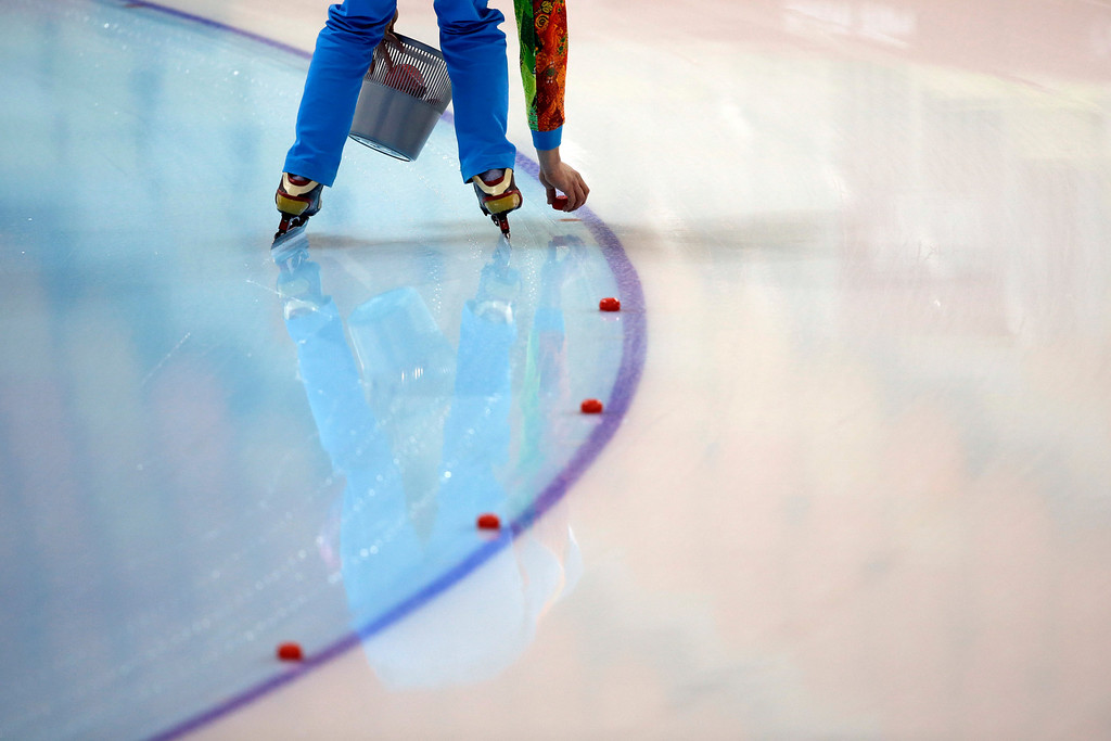 . A volunteer puts markers back on the ice after ice machines prepared the track for training races at the Adler Arena Skating Center during the 2014 Winter Olympics in Sochi, Russia, Wednesday, Feb. 5, 2014. (AP Photo/Patrick Semansky)