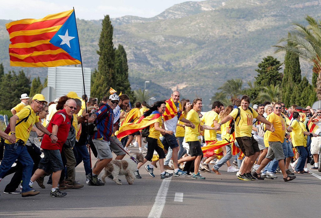 . Catalans react as they create a 400-kilometre (250-mile) human chain, part of a campaign for independence from Spain during Catalonia National Day, or Diada, in Alcanar, on September 11, 2013. Independence-seeking Catalans  marshalled their forces today to make a human link they say will stretch across 86 cities, towns and villages along the coast of the northeastern region on the Mediterranean, passing landmarks such as the Sagrada Familia basilica in Barcelona and the city\'s Camp Nou football stadium. JOSE JORDAN/AFP/Getty Images