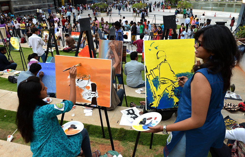 """. Indian artists participate in a painting movement titled \""""Colours of Mahatma\"""" held as part of the Gandhi Jayanthi Celebrations at a Mall in Bangalore on October 2, 2013.  144 artists took part in the painting marathon to mark the 144th birthday of The Father of the Nation, Mahatma Gandhi.   Manjunath Kiran/AFP/Getty Images"""