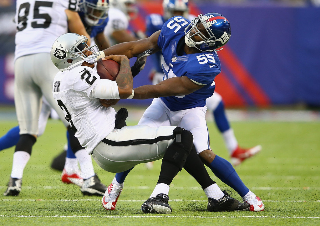 . Keith Rivers #55 of the New York Giants tackles  Terrelle Pryor #2 of the Oakland Raiders in the fourth quarter during their game at MetLife Stadium on November 10, 2013 in East Rutherford, New Jersey.  (Photo by Al Bello/Getty Images)