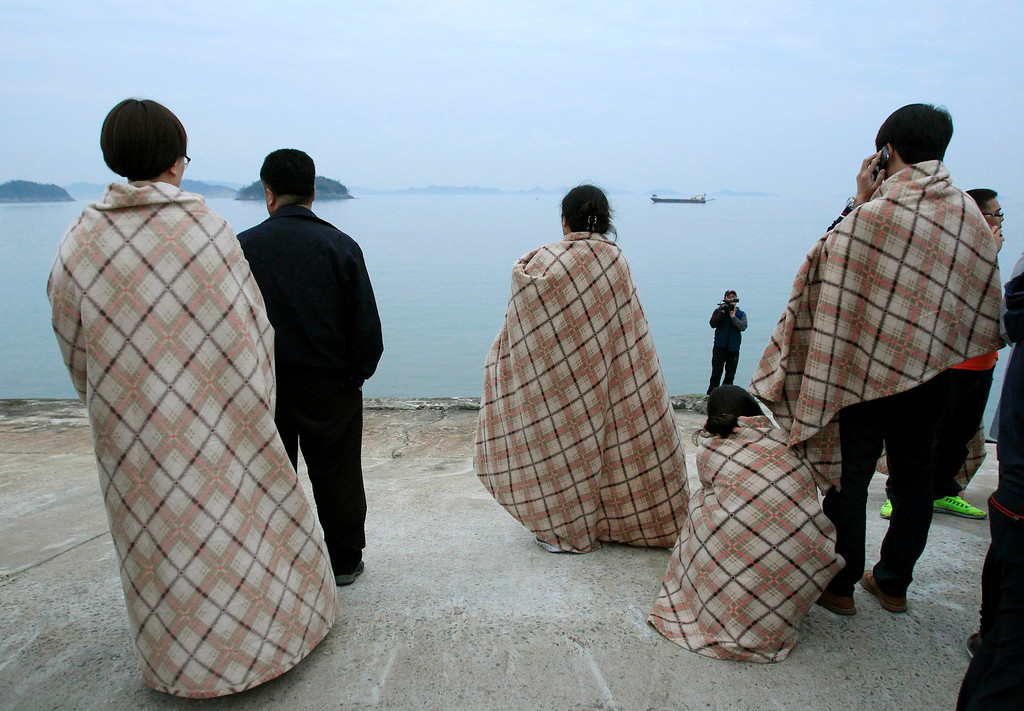 . Relatives wait for their missing loved ones at a port in Jindo, South Korea, Wednesday, April 16, 2014. A ferry carrying 459 people, mostly high school students on an overnight trip to a tourist island, sank off South Korea\'s southern coast on Wednesday, leaving nearly 300 people missing despite a frantic, hours-long rescue by dozens of ships and helicopters.  (AP Photo/Ahn Young-joon)