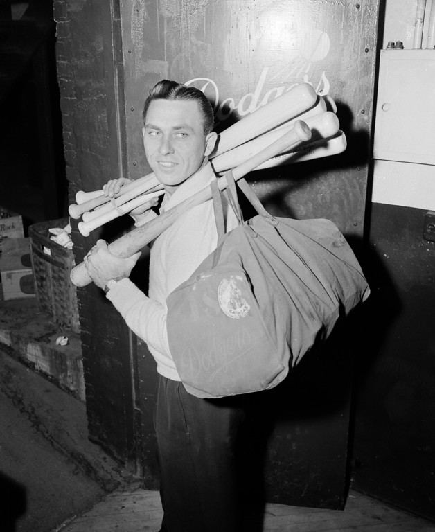 . Brooklyn Dodgers\' first baseman Gil Hodges is loaded down with bats and other equipment as he takes his last look at Ebbets Field in Brooklyn, N.Y., Oct. 6, 1953, after losing to the Yankees in the World Series.  (AP Photo/Jack Harris)