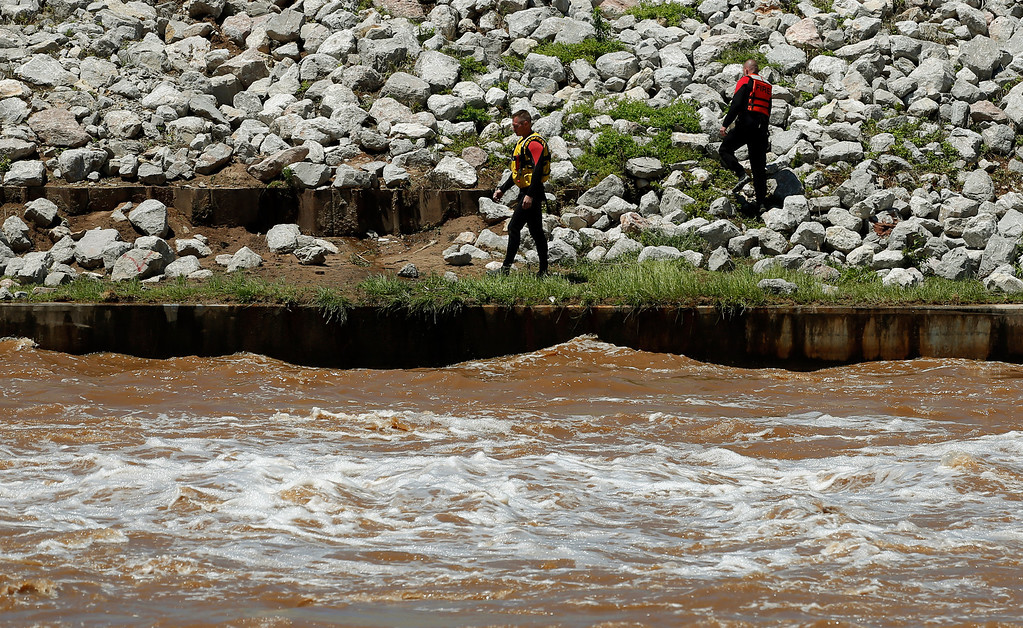 . Rescuers search for the bodies of a family in the Oklahoma River near May Ave. after they disappeared in storms that went through central Oklahoma Saturday, June 1, 2013 in Oklahoma City, (AP Photo/The Oklahoman, Sarah Phipps)