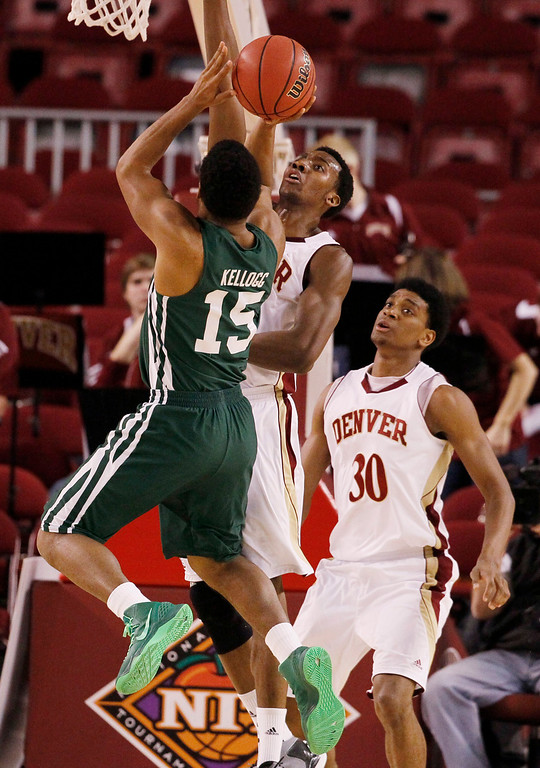 . Ohio guard Nick Kellogg, front, has his shot blocked by Denver forward Chris Udofia, center, as guard Cam Griffin looks on in the first half of a first-round NIT college basketball game in Denver on Tuesday, March 19, 2013. (AP Photo/David Zalubowski)