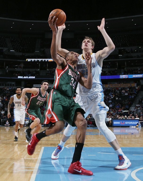 . Milwaukee Bucks forward Giannis Antetokounmpo, front, of Greece, has his shot blocked by Denver Nuggets center Timofey Mozgov, of Russia, in the first quarter of an NBA basketball game in Denver, Wednesday, Feb. 5, 2014. (AP Photo/David Zalubowski)