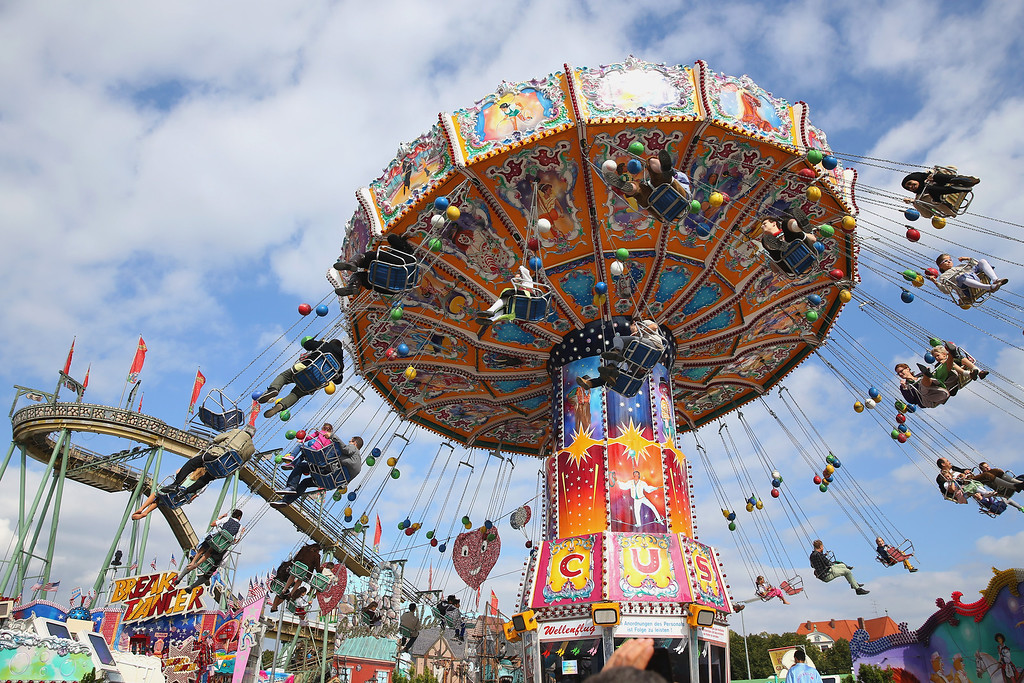 . People enjoy riding on a merry-go-round at the Oktoberfest on September 21, 2013 in Munich, Germany. The Munich Oktoberfest, which this year will run from September 21 through October 6, is the world\'s largest beer fest and draws millions of visitors.  (Photo by Alexander Hassenstein/Getty Images)