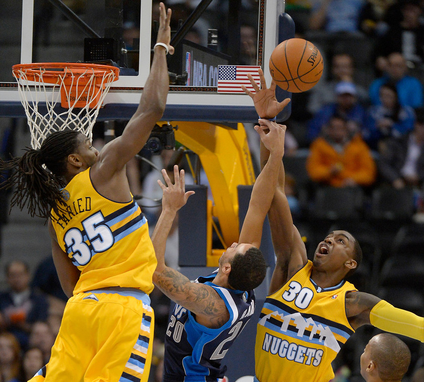 . Denver Nuggets small forward Quincy Miller (30) blocks a shot by Dallas Mavericks point guard Devin Harris (20) during the first quarter March 5, 2014 at Pepsi Center. Denver Nuggets power forward Kenneth Faried (35) also in on the play. (Photo by John Leyba/The Denver Post)