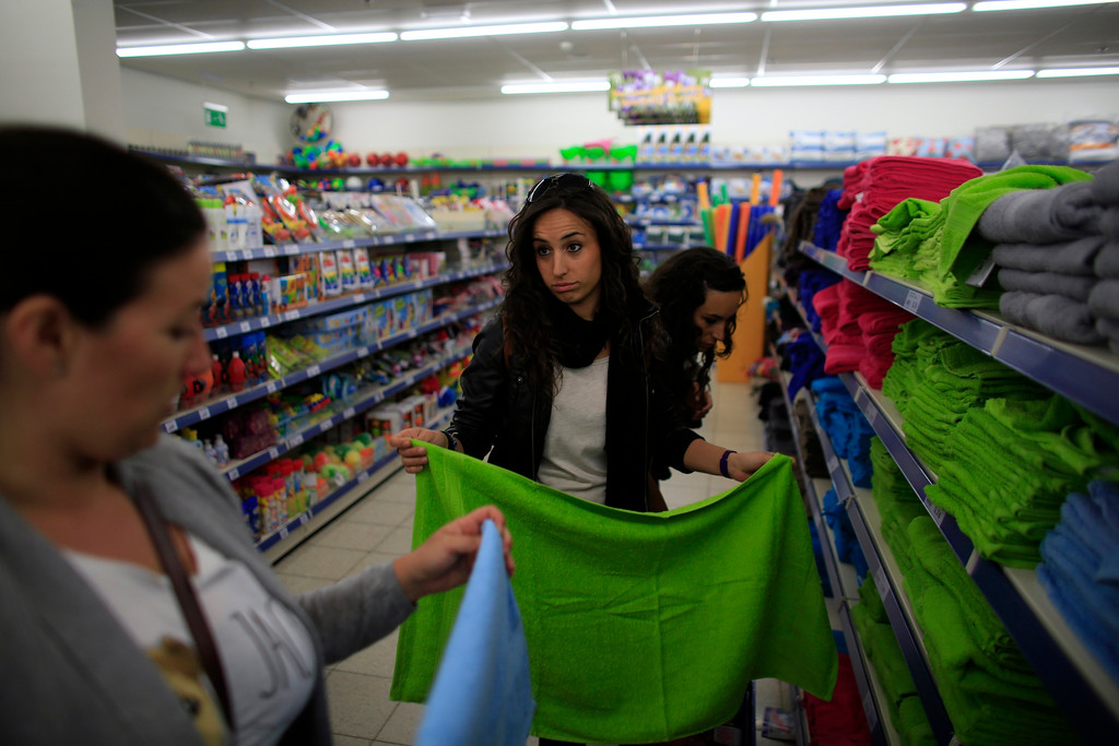. Spanish nurses Maria Jose Marin (C), 23, holds up a towel as she stands next to her twin sister Maria Teresa (R) in a supermarket in The Hague, June 7, 2013. After months of studying Dutch, a group of young Spanish nurses moved to the Netherlands to take up work, fleeing a dismal job market at home. Spain\'s population dropped last year for the first time on record as young professionals and immigrants who moved here during a construction boom head for greener pastures. Spain\'s jobless rate is 27 percent, and more than half of young workers are unemployed. For Spanish nurses, the Netherlands\' nursing deficit is a boon. Picture taken June 7, 2013. REUTERS/Marcelo del Pozo