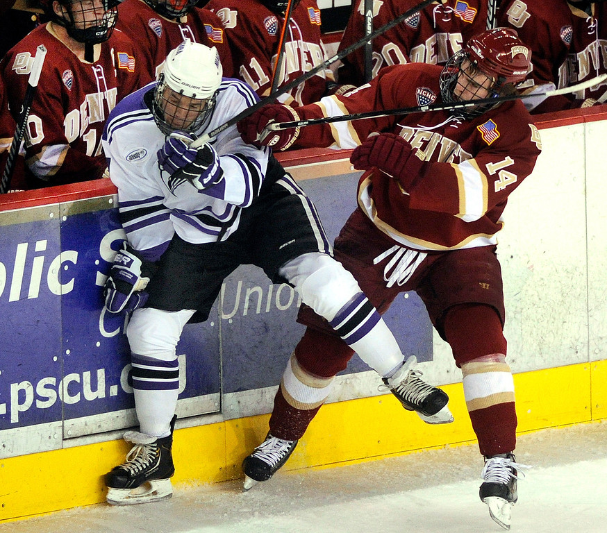 . DENVER, CO. - OCTOBER 25: Denver wing Larkin Jacobson (14) pushed Niagara wing Isaac Kohls (27) into the boards in front of the Pioneers bench in the second period. The University of Denver hockey team hosted Niagara at Magness Arena Friday night, October 25, 2013. Photo By Karl Gehring/The Denver Post
