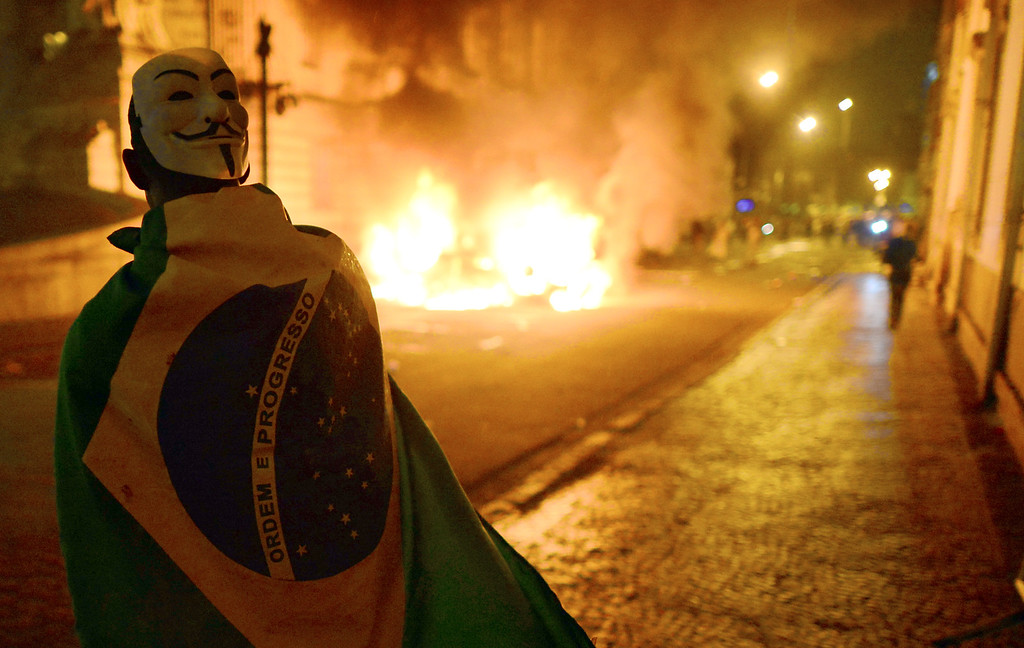 . A demonstrator walks wrapped in a Brazilian national flag during clashes with the riot police in downtown Rio de Janeiro on June 17, 2013, after a protest against higher public transportation fares and the use of public funds to finance international football tournaments. Protesters in several major cities are up in arms over hikes in mass transit prices -- from $1.5 to $1.6 -- as well as over the $15 billion earmarked for the two sports events amid calls for more health and education funding.   CHRISTOPHE SIMON/AFP/Getty Images