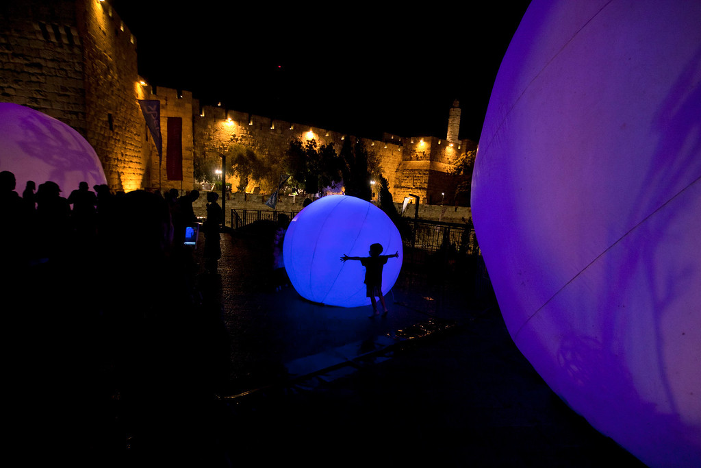 . A child hugs a light installation at the Jaffa gate during the fifth annual Festival of Light in Jerusalem\'s Old City,  Wednesday, June 5, 2013. (AP Photo/Sebastian Scheiner)